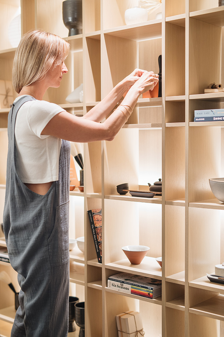 woman adjusting the decor on a shelf at Bloom